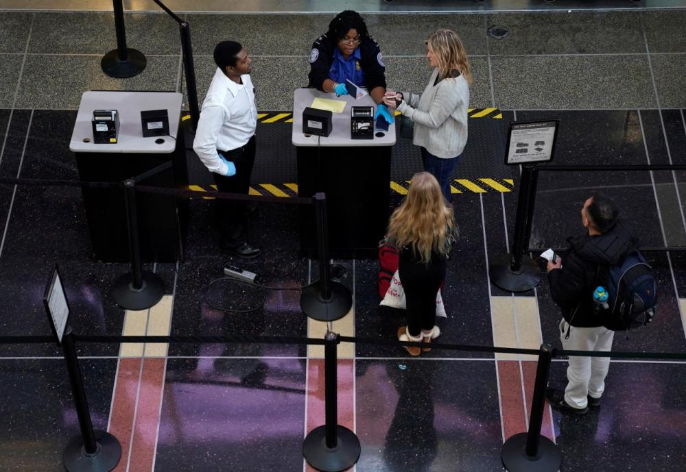 An employee with the Transportation Security Administration (TSA) checks the documents of a traveler at Reagan National Airport in Washington